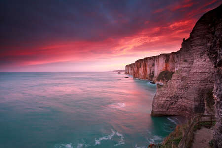 dramatic sunrise over ocean and cliffs, Etretat, France photo