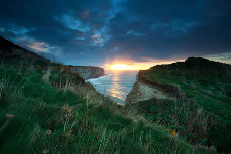 sunset sunshine over cliffs in ocean, Normandy, France photo