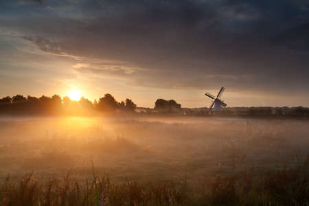 early morning: misty sunrise and Dutch windmill, Netherlands Stock Photo