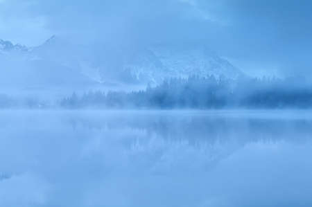 mountains reflected in lake in dense dusk fog, Germany photo