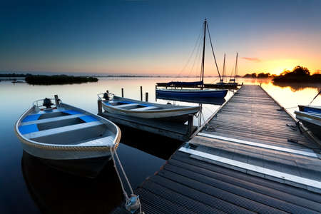 sunrise over lake harbor with boats and pier Stockfoto