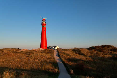 road to red lighthouse and blue sky, Netherlands Stockfoto