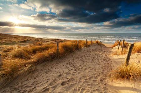 zonsondergang over zandpad naar Noord-zee, Holland Stockfoto