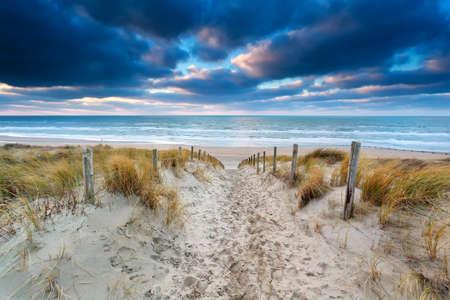 zandpad naar Noordzeekust bij zonsondergang, Noord-Holland, Nederland