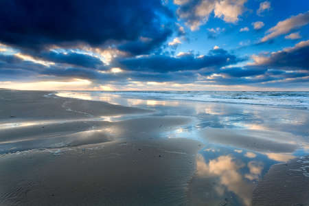blue sky cloudscape reflected in North sea, Holland