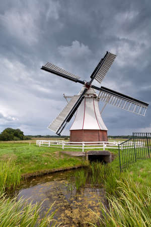 clouded: white windmill by river over clouded sky, Holland