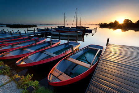 water  scenic: boats by pier at harbor during sunrise, Netherlands