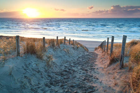 holland: sunset over path to North sea beach, North Holland, Netherlands