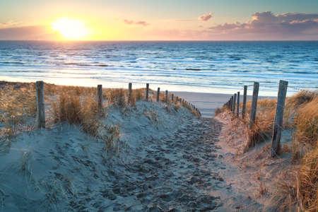 zonsondergang over weg naar Noord-zee strand, Noord-Holland, Nederland