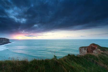岩の海岸の夕日、ノルマンディー、フランスで
