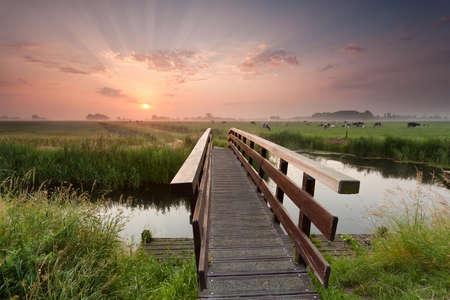 prachtige zonsopgang boven fietsbrug in landbouwgrond, Nederland