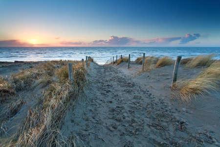zandpad naar Noord-zee strand bij zonsondergang, Holland Stockfoto