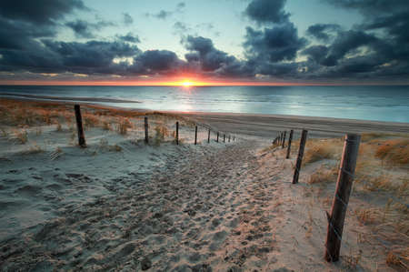 sand path to North sea beach at sunset, Netherlands