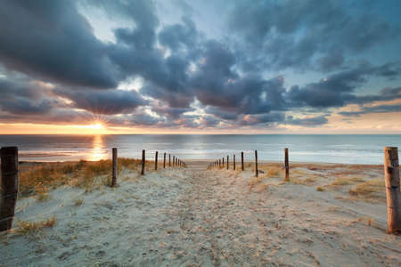 romantic path to sand beach at sunset, North Holland, Netherlands