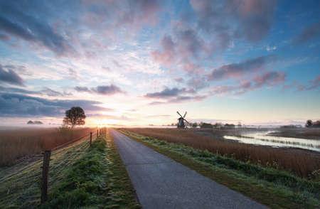 racefiets, windmolen in zonsopgang, Holland Stockfoto