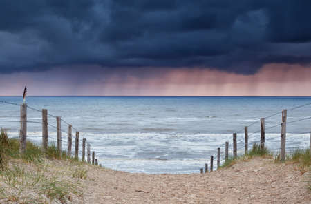 storm coming: rain and storm coming from North sea to beach, Holland