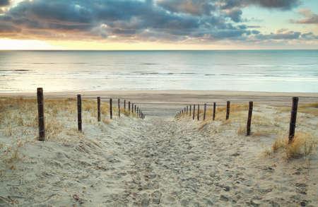 zand pad naar de Noordzee bij zonsondergang, Holland Stockfoto