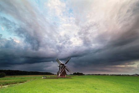 dark stormy clouds over windmill, Netherlands Stock Photo