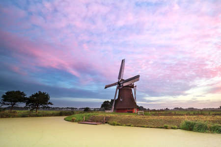 holland windmill: old windmill by lake at sunrise, Holland