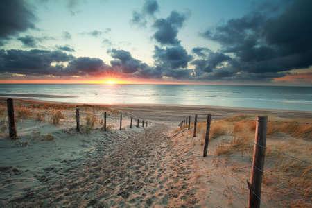 夕暮れ時、オランダ海ビーチに砂の道