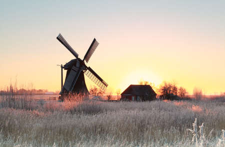 sunrise over frosted meadow and windmill in winter Stock Photo