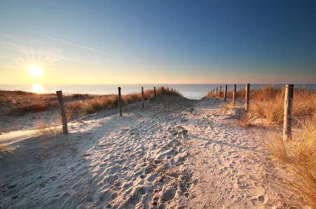 sunlight over sand path to North sea beach, Holland Stock Photo