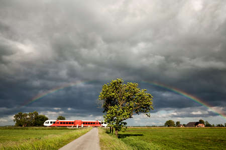 rainbow over railroad with train, Netherlands Stock Photo - 80236298