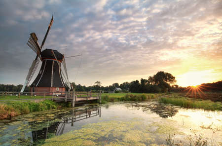 morning sunshine over samll pond and windmill in Holland