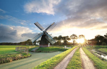 windmill, rural road and river at sunrise, Netherlands Stock Photo