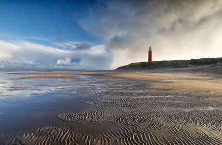 beautiful stormy sky over North sea beech and lighthouse