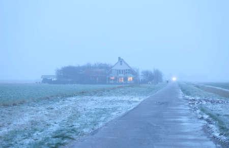 Dutch farmhouse in wintry dusk 写真素材