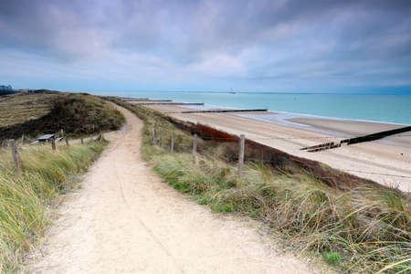 path on dune over North sea beach on gloomy day Banco de Imagens