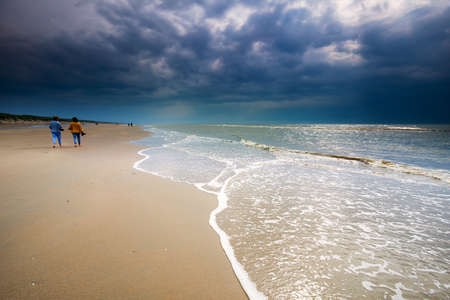 couple walking along the beach in sunshine, Zandvoort, Holland