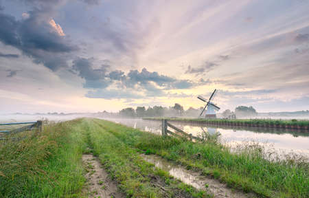 beautiful morning over charming windmill by river, Holland