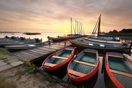 beautiful sunrise over lake with pier, boats and yachts Banco de Imagens