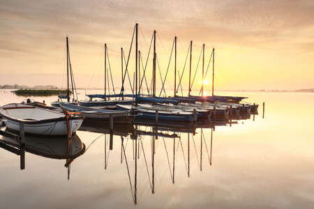 beautiful serene sunrise over lake with yachts by pier Stock fotó