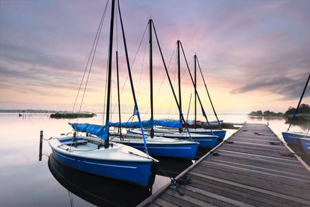 few yachts by pier at dawn in summer, Netherlands Banco de Imagens