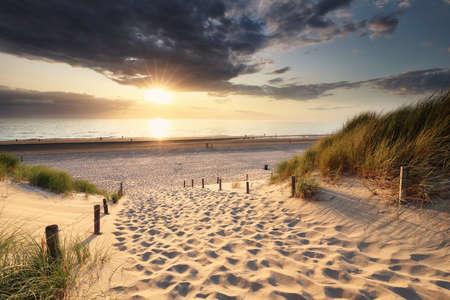 golden sunset light over sand path to North sea beach between dunes