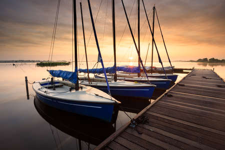 serene charming harbor at sunrise with yachts by pier