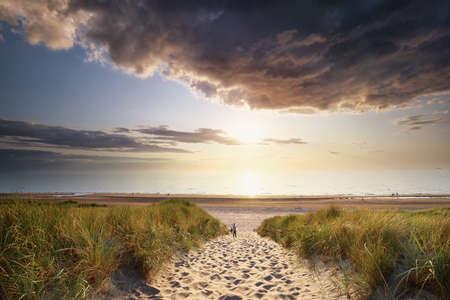 gold sunset sunlight over sand path to north sea beach, Netherlands Banco de Imagens