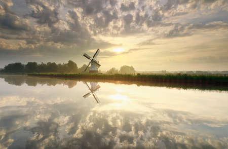 sunrise over white Dutch windmill and river in summer Banco de Imagens