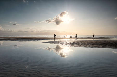 people silhouettes on sea beach against sun in summer
