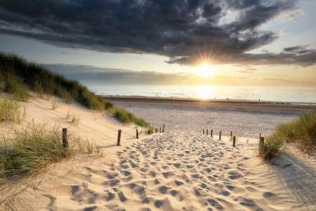 path on sand to North sea beach at sundown, Holland Banco de Imagens