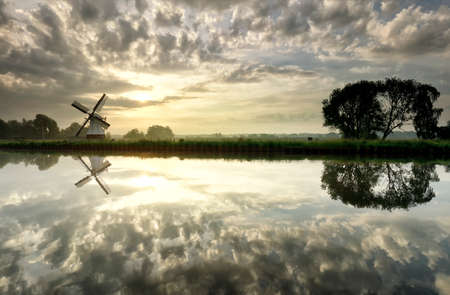 Dutch windmill by river at sunrise with reflected clouds in water, Holland