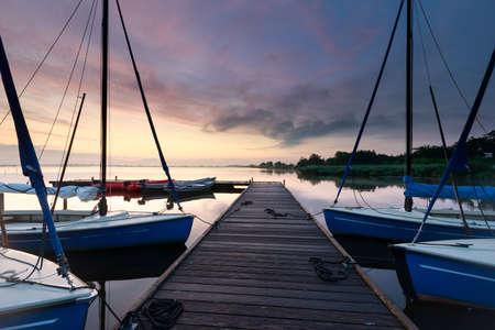 yachts on big lake harbor at sunrise in summer