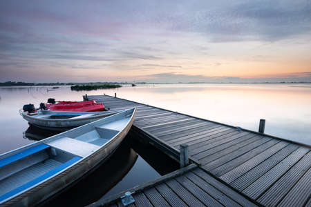 boat at pier on big lake during sunrise in summer