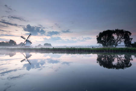white windmill by river with sky reflection at dawn Banco de Imagens