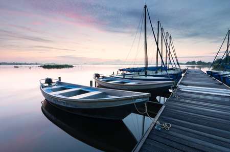 yachts by pier on big lake at dawn in summer