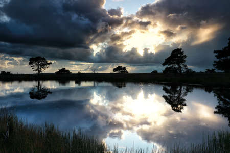 dramatic stormy clouds over wild lake in summer Banco de Imagens