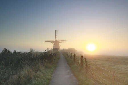 misty gold sunrise behind Dutch windmill, Netherlands